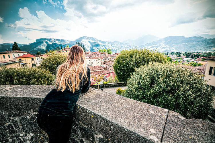 Young woman overlooking the terrace of Barga, Lucca, Tuscany, admires the mountains on the horizon Blonde Lonely Lucca Italy Relaxing Thinking Tuscany City Cityscape Day Girl Hair Leisure Activity Lifestyles Long Hair Looking At View Mountain Nature Outdoors Plant Real People Rear View Relax Sky Standing Tree
