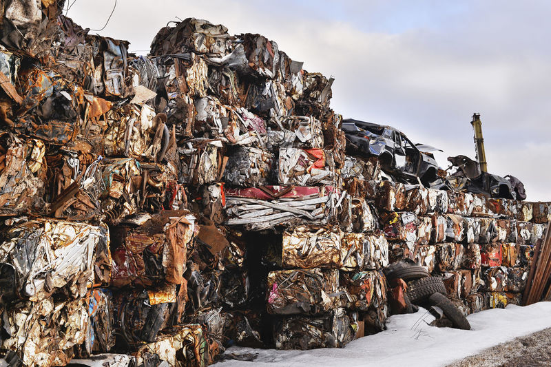 Stack of garbage by metal structure against sky
