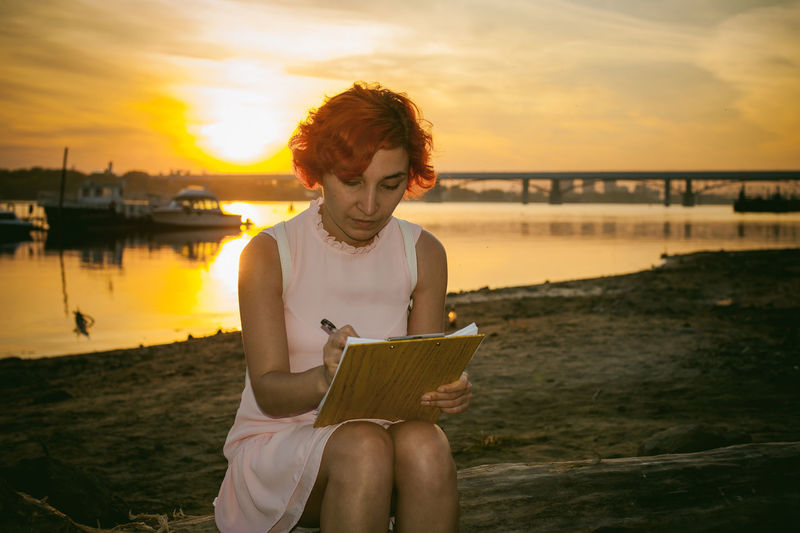 Mid adult woman writing while sitting at riverbank against sky during sunset