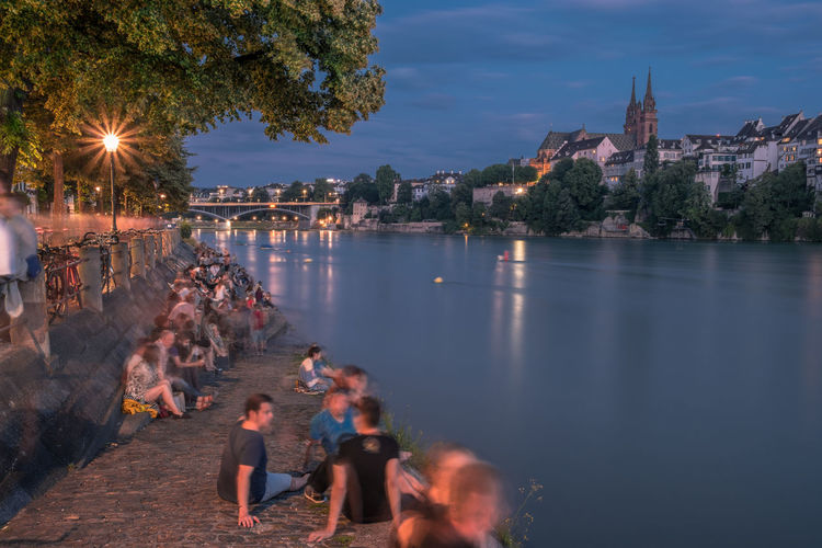 People on illuminated city by river against sky