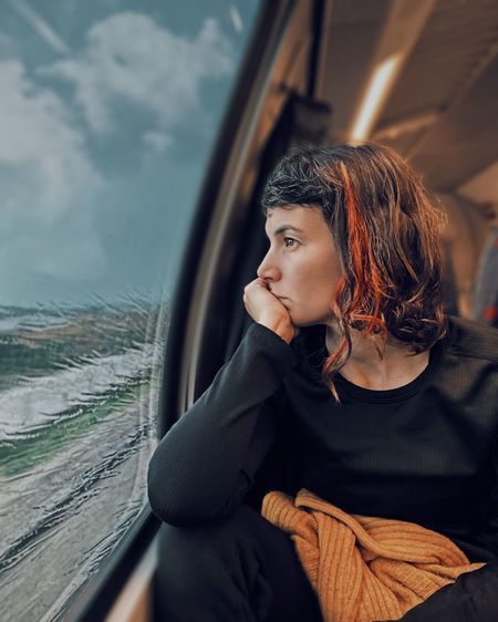 Woman looking away while sitting in car window