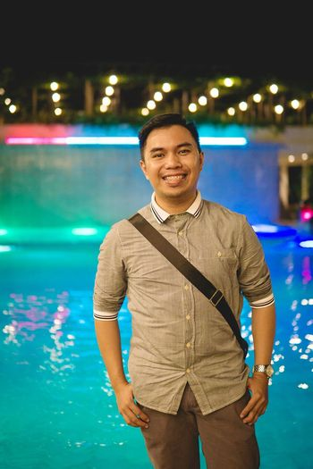 Portrait of young man standing against swimming pool