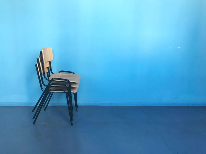 Stacked chairs in blue corridor Chairs Three Objects Multiple Objects Chairs Blue Color Stacked Blue Seat Chair No People Wall - Building Feature Absence Indoors  Empty Copy Space Day Built Structure Flooring Wood - Material Blue Background Still Life Wall