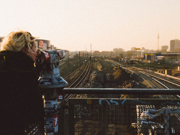 Side View Of Woman Looking In Coin-Operated Binoculars At Railroad Tracks