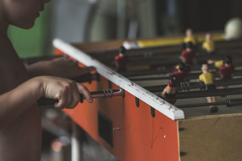 Close-up of boy playing foosball