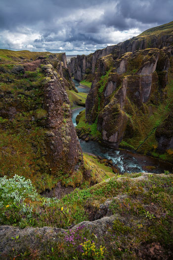 Scenic View of Fjadrargljufur Canyon in South Iceland summer. Cloudy Dramatic Sky Fjadrargljufur Fjaðrárgljúfur Fjaðrárgljúfur Canyon Hiking Iceland Adventure Canyon Cliff Flower Hi Hike Icelandic Journey Mountain River Summer Waterfall Waterfalls