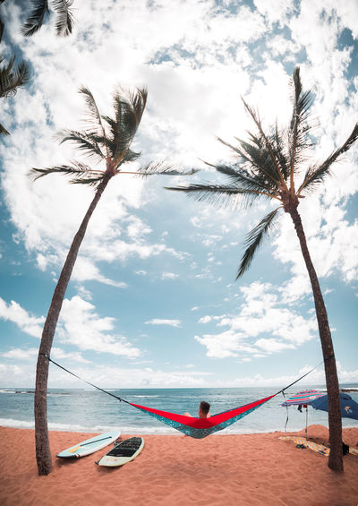 Man on hammock by palm trees at beach against sky