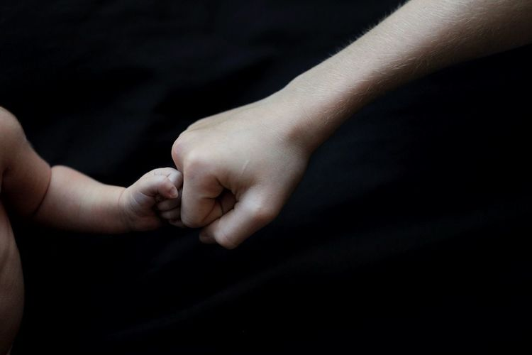 Close-up of mother and baby bumping fist over black background