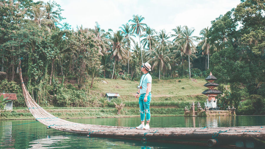 Man standing on wooden raft over lake