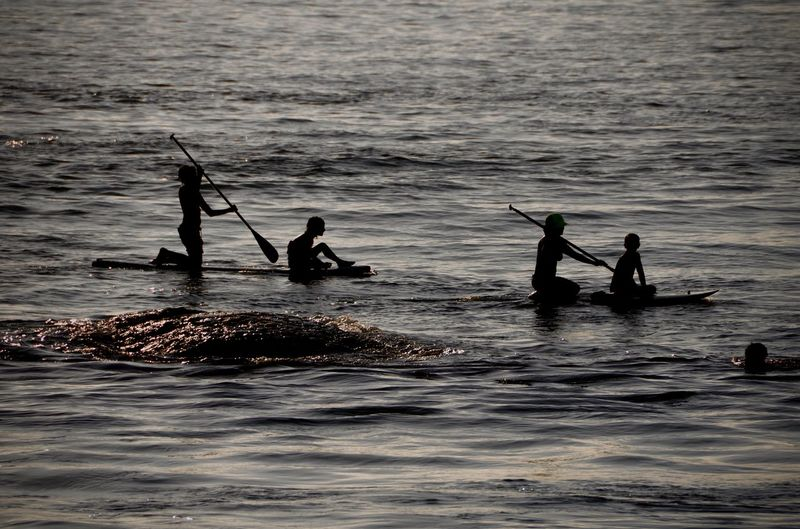 Silhouette people enjoying in sea