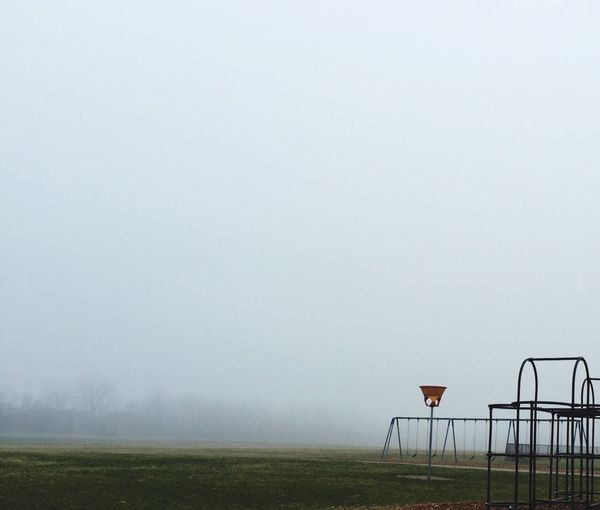 Outdoor play equipment on playground against sky during foggy weather