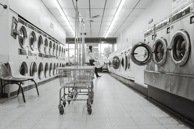 Woman carrying laundry basket at laundromat