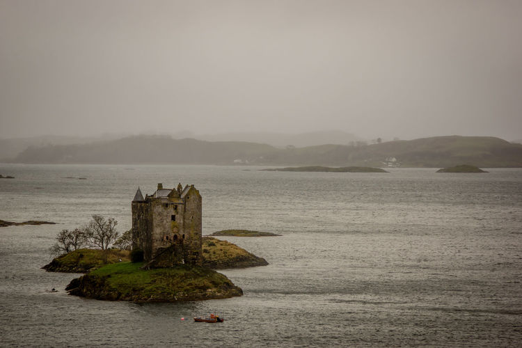 Castle Stalker Amidst Sea Against Sky