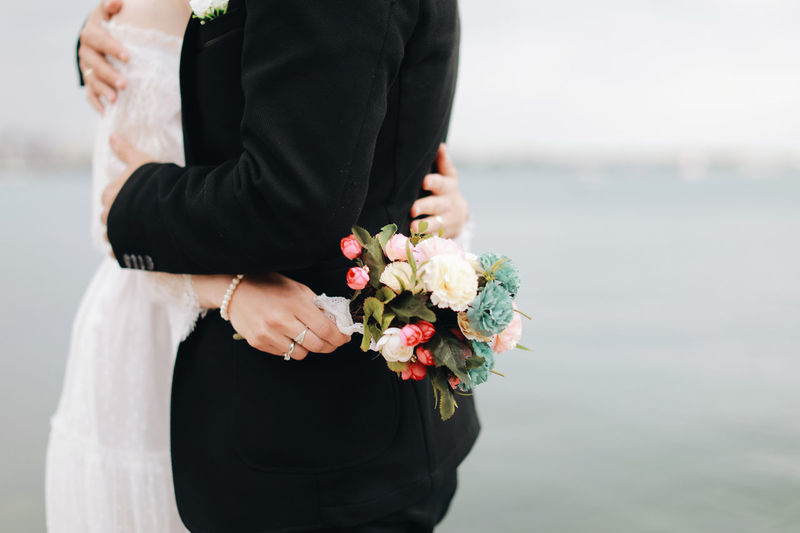 Midsection Of Newlywed Couple Embracing While Standing By Sea Against Sky