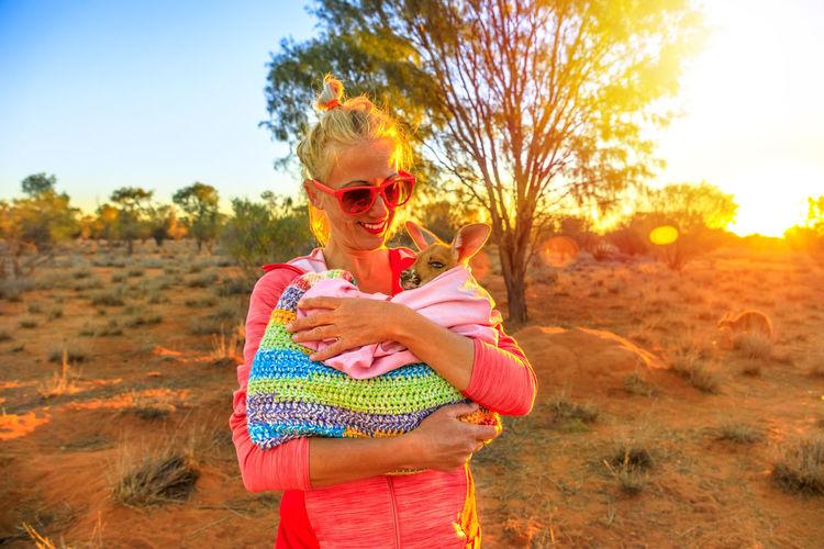 Smiling woman holding kangaroo on field during sunset