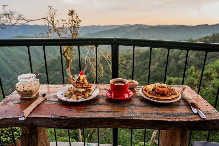 Breakfast on table by railing against sky
