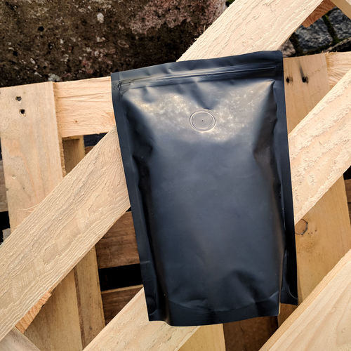 Black unbranded bag of coffee on wooden planks