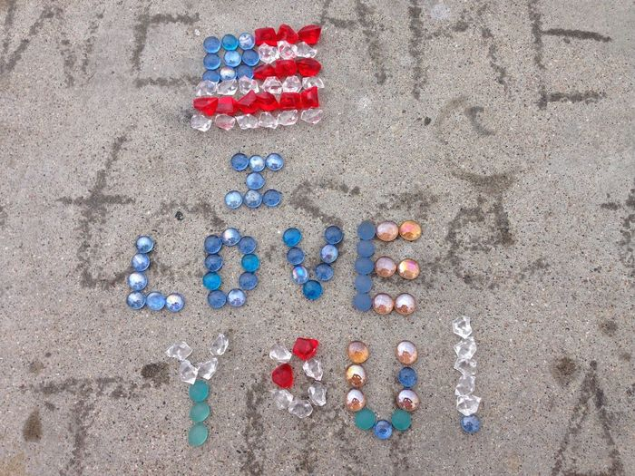High angle view of american flag and text made with crystals on sand