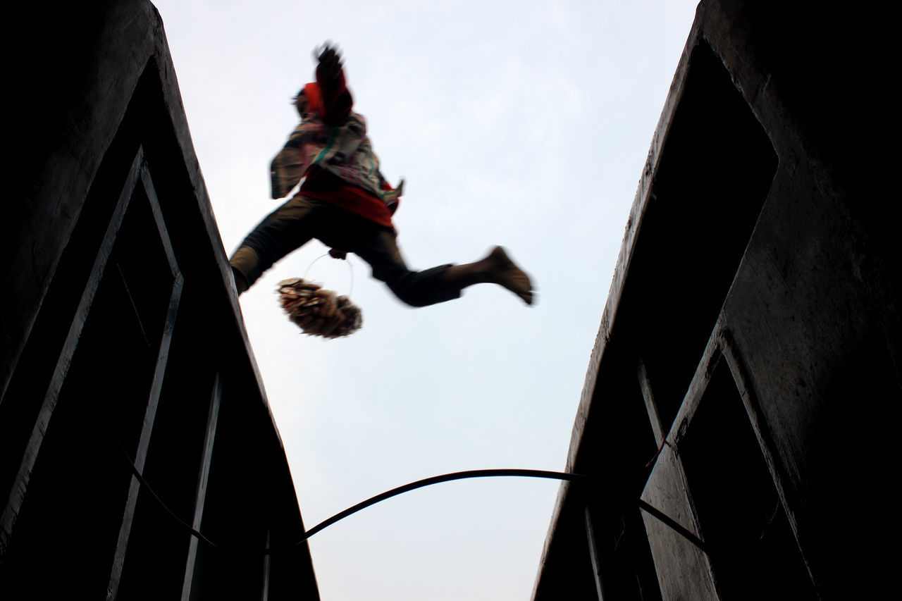 Low Angle View Of Vendor Jumping On Train Against Clear Sky