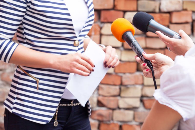 Cropped hands of journalists interviewing woman