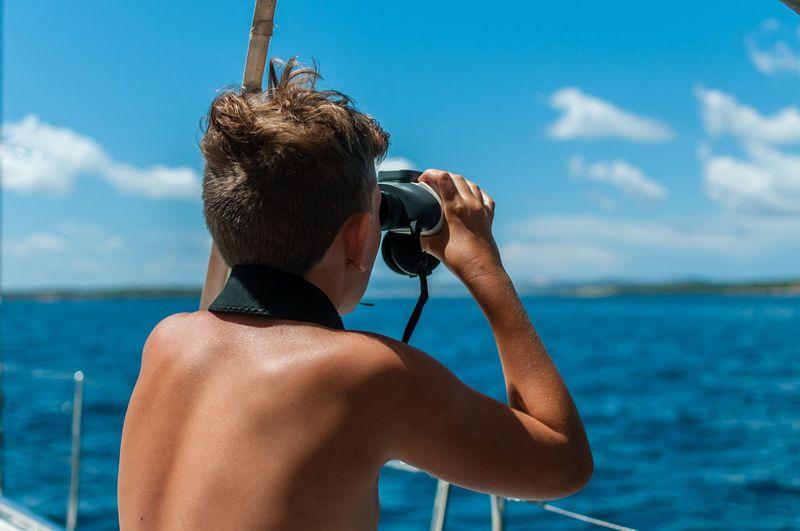 Rear view of shirtless boy looking through binoculars on boat at sea