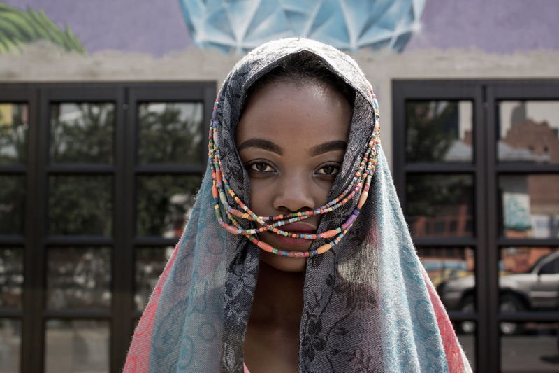 Close-up portrait of young woman wearing headscarf with beads