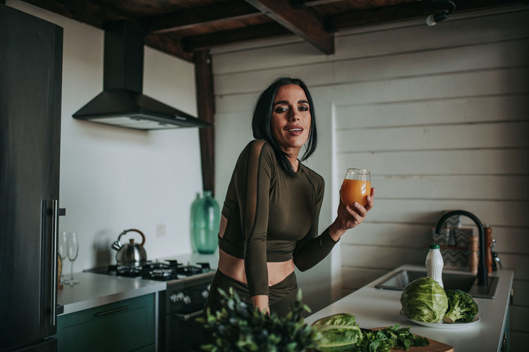 Portrait of smiling woman standing in kitchen at home