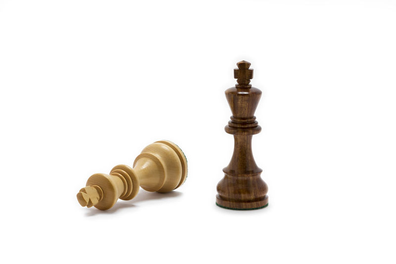 Low angle view of chess pieces against white background