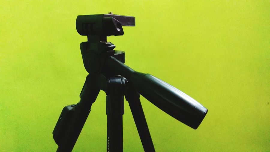 Close-up of camera photographing against green background