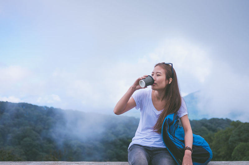 Young woman using phone while standing on mountain against sky