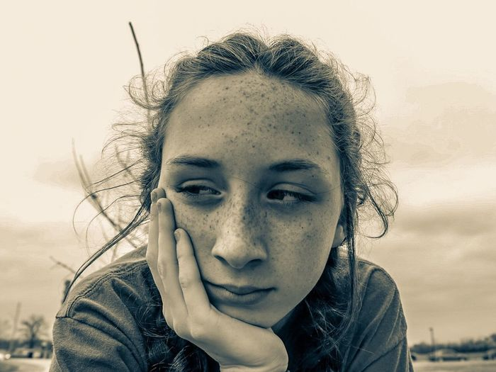 Close-up of thoughtful teenage girl against cloudy sky