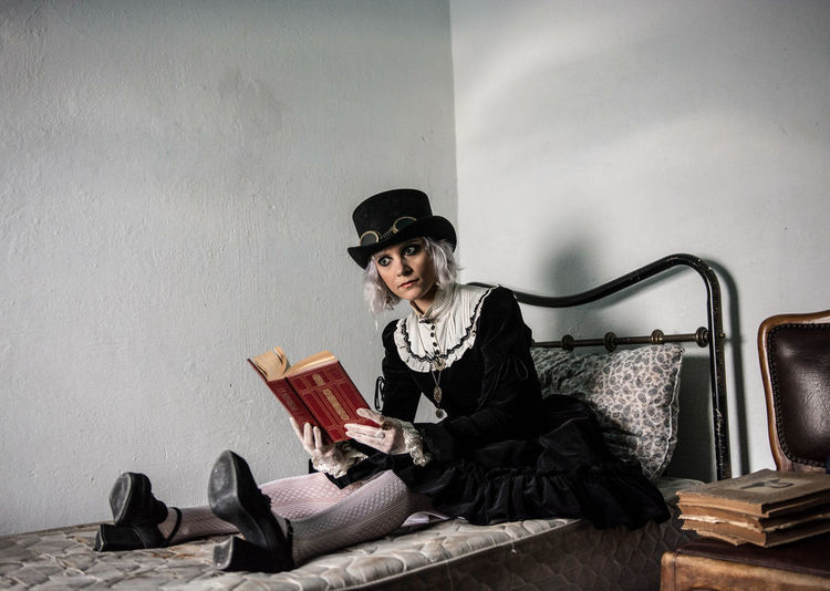 Woman in steampunk outfit sitting in bed while holding a book. Sitting One Person Indoors  Hat Front View Young Adult Clothing Women Book Beautiful Woman Looking At Camera Steampunk Doll Creepy Bedroom Reading Old Book Hat Black Dress Gloves Scary Fashion Beauty Mannequin