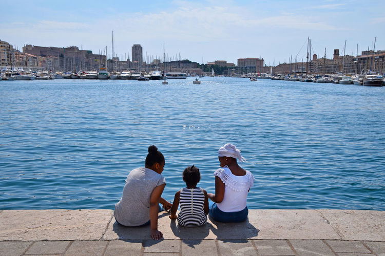 Afro-European family on sea quay marina Water Rear View Real People Sitting City Women Lifestyles Togetherness Sky Nature Adult Leisure Activity Day Outdoors Cityscape Looking At View Sister Family Afro American Afroamerican Girl Black Quay Marina Copy Space Three People Streetwise Photography The Art Of Street Photography