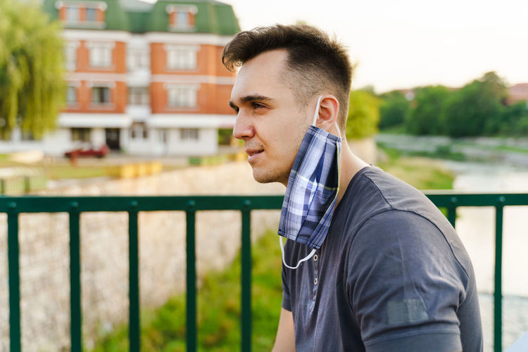 Portrait of young man standing against railing