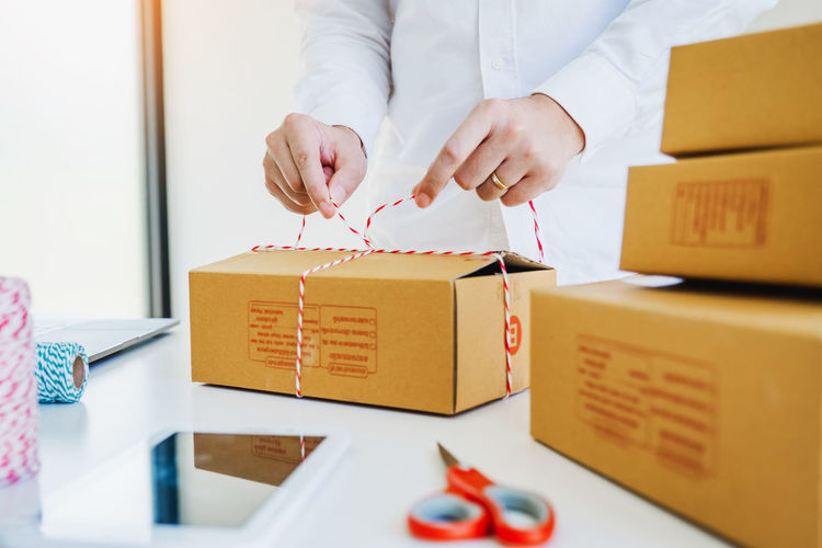 Woman packing cardboard boxes at desk in office