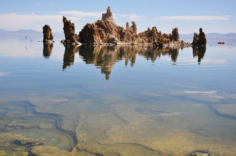 Reflection Of Rocks In Water Against Sky
