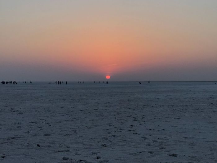 White Desert. White Rann Sunset Beauty In Nature Scenics Nature Horizon Over Water Tranquil Scene Tranquility Idyllic Sky Outdoors Sun Vacations Clear Sky No People Travel Destinations Day