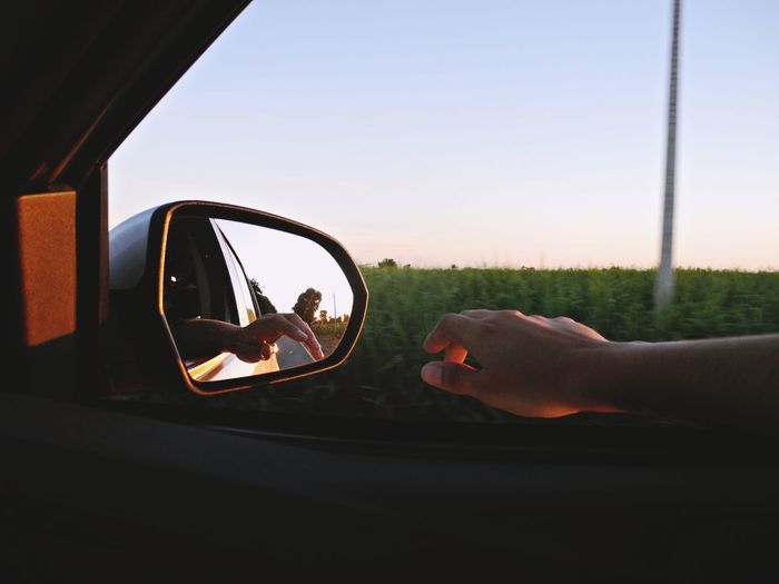 Close-up of person in car against sky