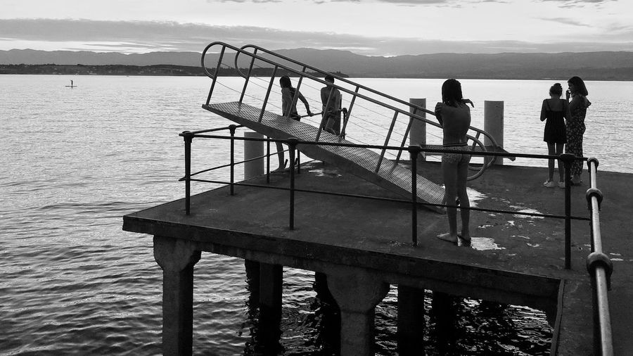 Rear view of people on pier over sea against sky