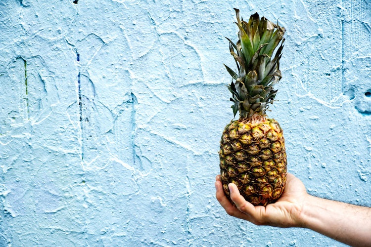 Cropped hand holding pineapple against wall