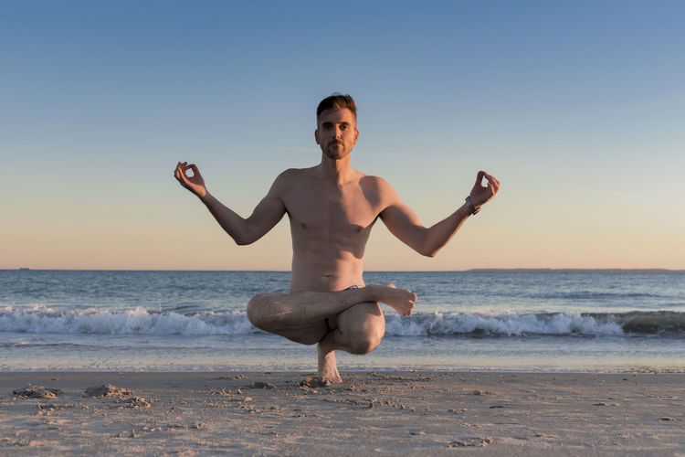 Man doing lifted Lotus yoga pose at the beach with gradient sky Muscular Build Lifestyle Fitness Health Pose Sunset Beach Yoga Beach