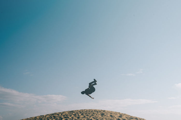 Low angle view of man jumping on hill against sky