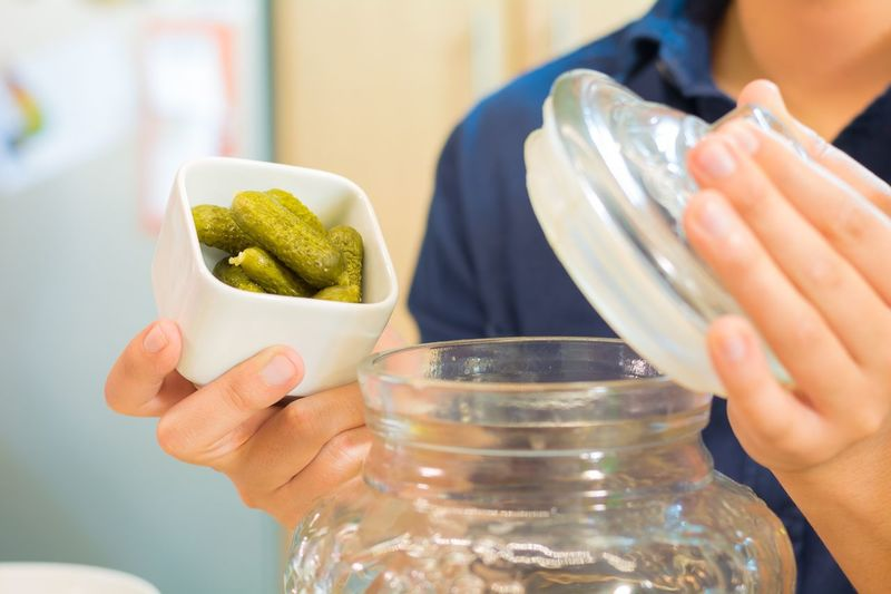 Midsection of person putting pickled cucumbers in jar