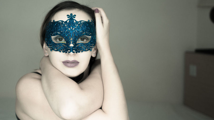 Portrait of young woman wearing venetian mask at home
