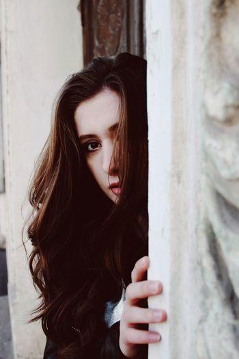 Portrait of woman peeking through window