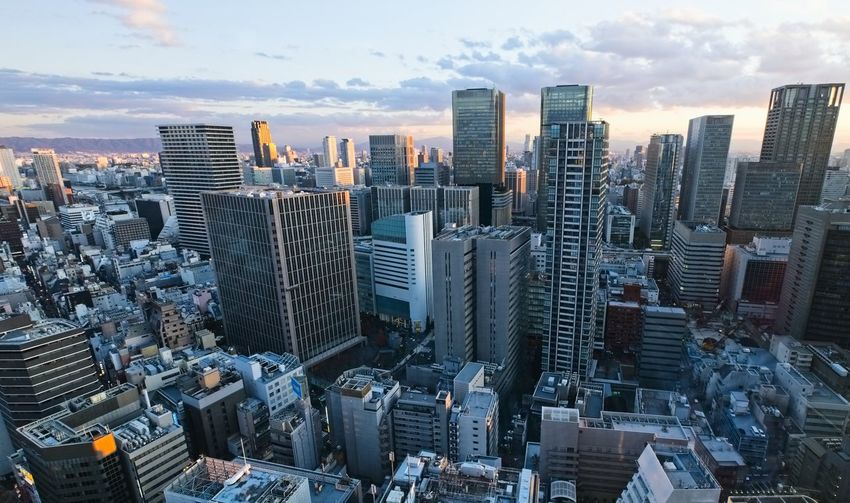 Bird aerial view of modern city high rise building agaist the sky