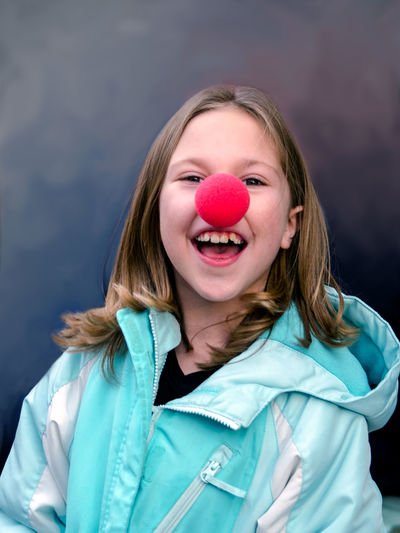 an adorable girl sports a red foam nose as she participated in a campaign to end childhood poverty called red nose day Funny Happy Red Nose Day Adorable Blond Hair Childhood Children Only Close-up Comic Releif Day Ending Child Poverty Foam Nose Front View Fundraising Campaign Headshot Looking At Camera One Girl Only One Person People Portrait