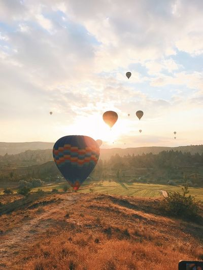 Cappadocia Turkey Air Vehicle Balloon Ballooning Festival Beauty In Nature Cloud - Sky Environment Field Flying Hot Air Balloon Land Landscape Mid-air Mode Of Transportation Nature No People Non-urban Scene Outdoors Scenics - Nature Sky Sun Sunlight Tranquil Scene Transportation EyeEmNewHere