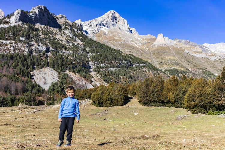 Portrait of boy standing on field against mountains