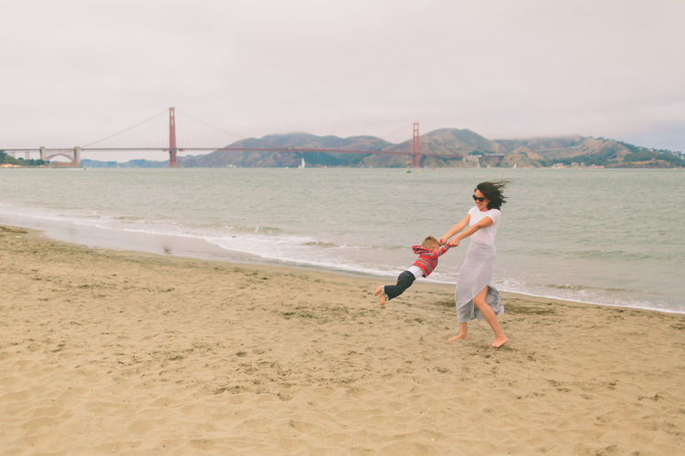 Full Length Of Playful Mother Spinning Son At Beach